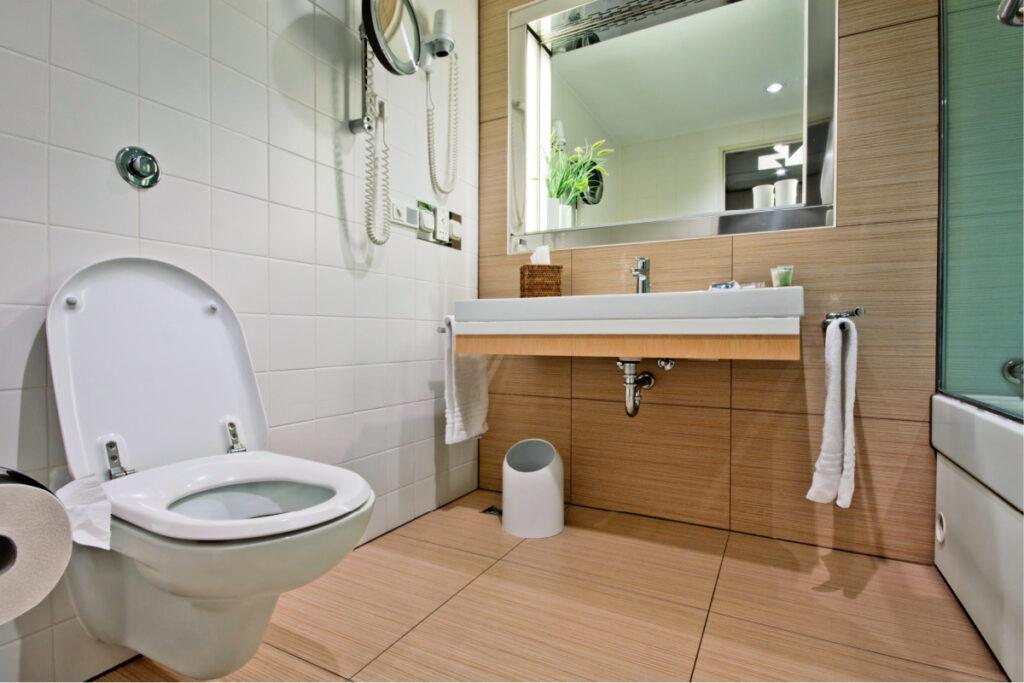 Baño moderno con inodoro y lavabo de pared