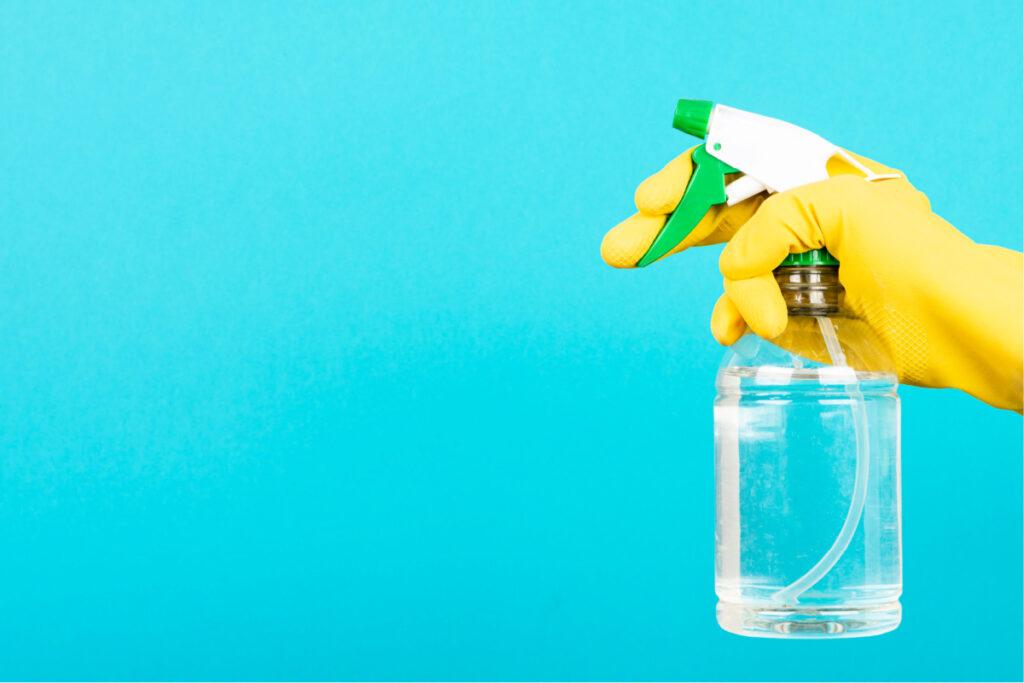 Mano en guante de goma sosteniendo una botella llena de alcohol isopropílico para usar como limpiador casero