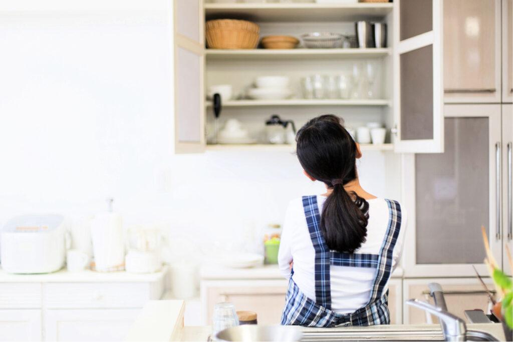 Mujer en la cocina moderna mirando mirando el armario abierto mientras se prepara para organizar sus armarios de cocina