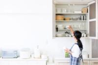 Mujer organizando armario de cocina