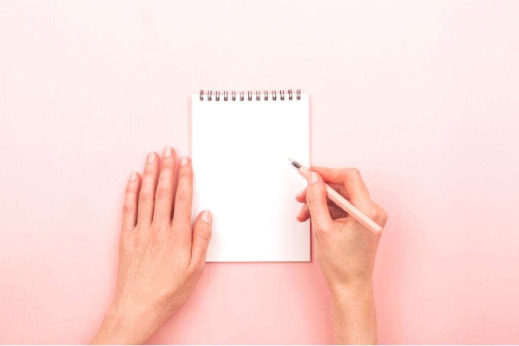 Vista aérea de las manos de una mujer sosteniendo un cuaderno blanco y un lápiz rosa