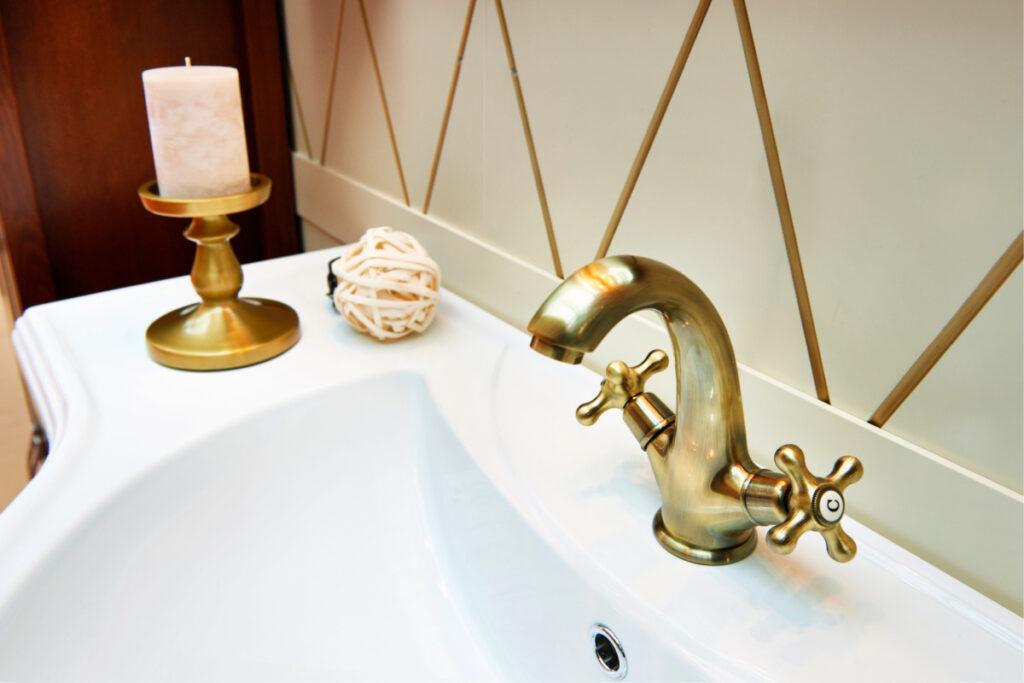 Limpie el grifo del lavabo del baño de latón con un candelabro de latón lacado cerca