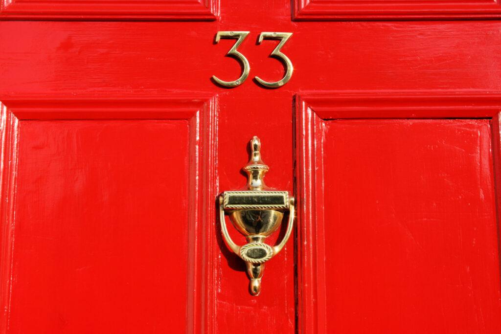 Martinete de latón limpio y brillante en una puerta roja