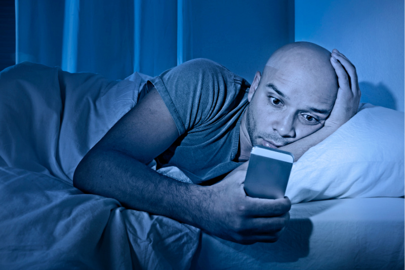 Un hombre en la cama despertado por un teléfono brillante muestra por qué no debes tenerlos en tu habitación