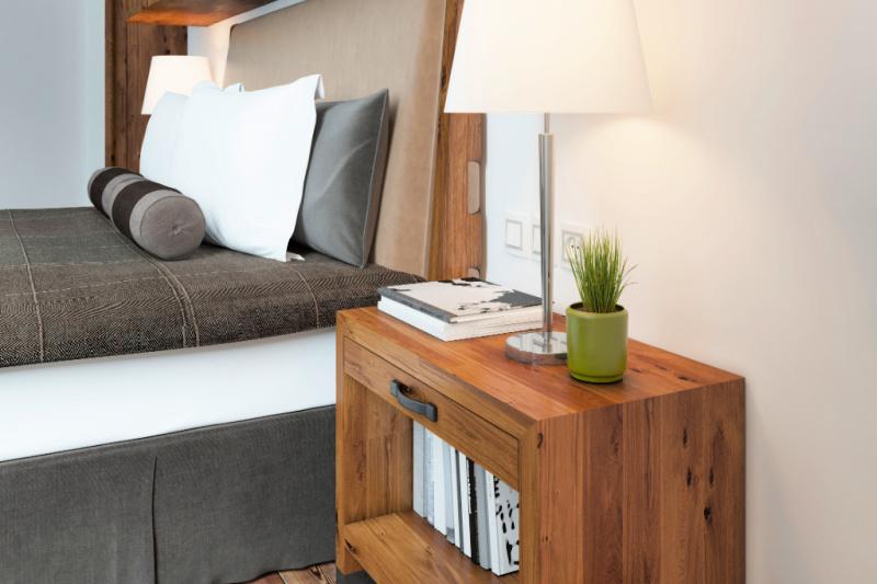 Una cama al lado de una mesita de noche con libros que ocupan la mayor parte de la parte superior y un estante completo debajo