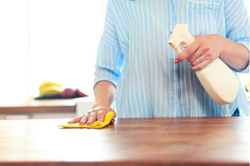 Mujer sosteniendo una botella de limpiador en aerosol en una mano y limpiando el mostrador con la otra