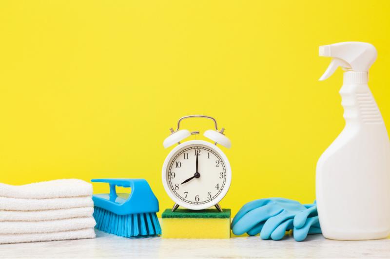 Despertador antiguo blanco y herramientas de limpieza contra un fondo amarillo brillante