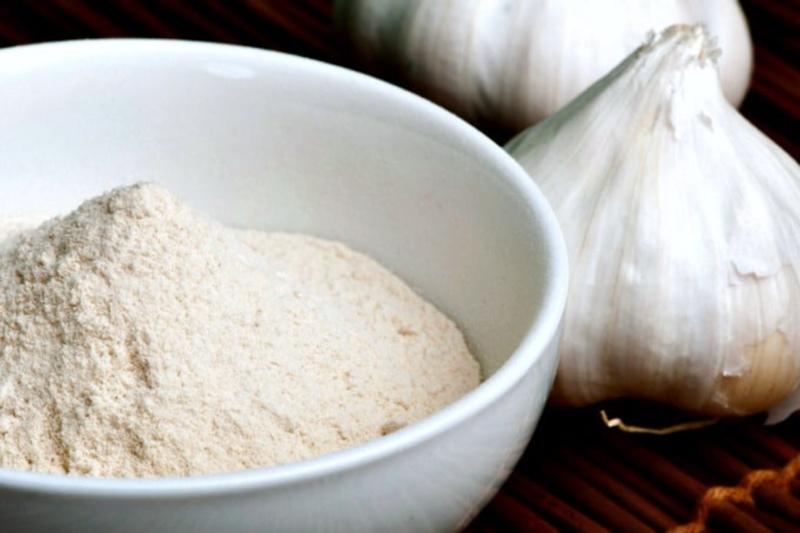 Primer plano de ajo en polvo casero en un recipiente junto a dos cabezas de ajo
