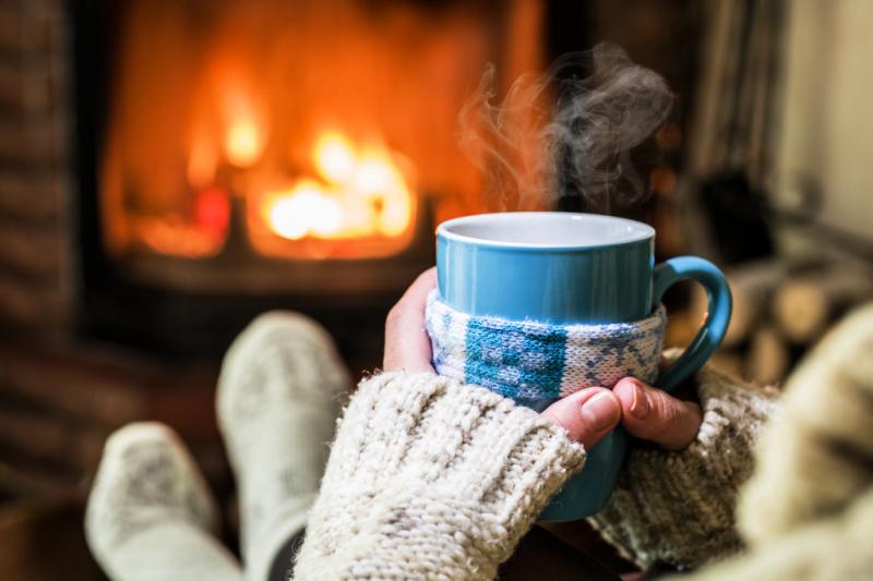 Primer plano de las manos de la mujer sosteniendo la taza mientras se sienta frente a la chimenea de leña