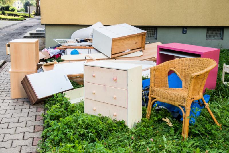 Un montón de muebles y otros desorden en el césped junto a una acera