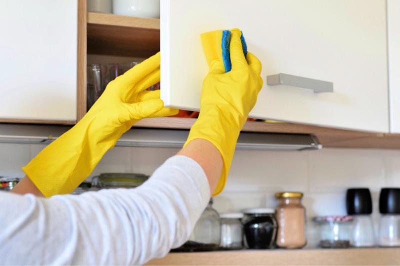 Mujer con guantes de goma y esponja para limpiar la puerta del armario de cocina