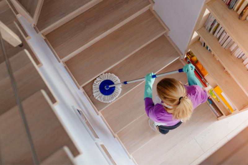 Vista aérea de la mujer con un trapeador para limpiar escaleras de madera