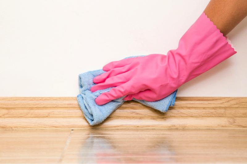 Mano en guante de goma limpiando el rodapié con un paño de limpieza