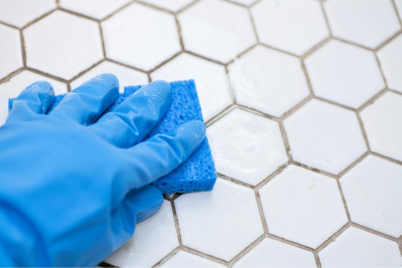 Mano en un guante de goma sosteniendo una esponja usando un truco de limpieza rápida para limpiar la lechada