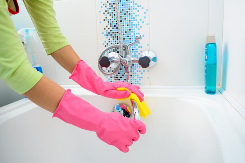 Mujer con guantes y con un paño para limpiar el grifo de la bañera