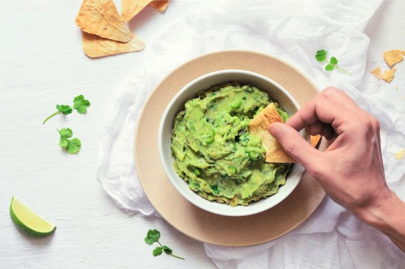 Mano de mujer sosteniendo un chip de tortilla para sacar guacamole auténtico de un cuenco de madera. Se esparcen a su alrededor chips de tortilla, cilantro y una rodaja de limón para decorar.