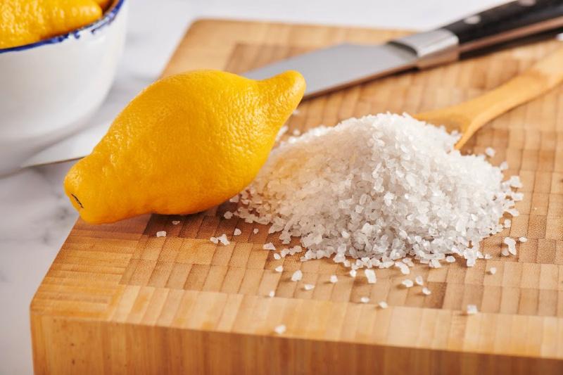 Un limón, un cuchillo y un montón de sal gruesa sobre una tabla para cortar madera
