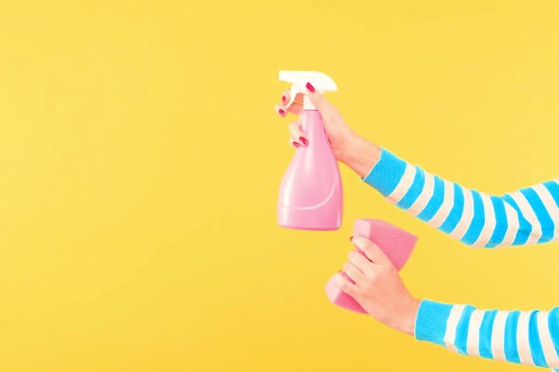 Imagen de las manos de una mujer sosteniendo una botella de spray y una esponja para acelerar la limpieza de la casa