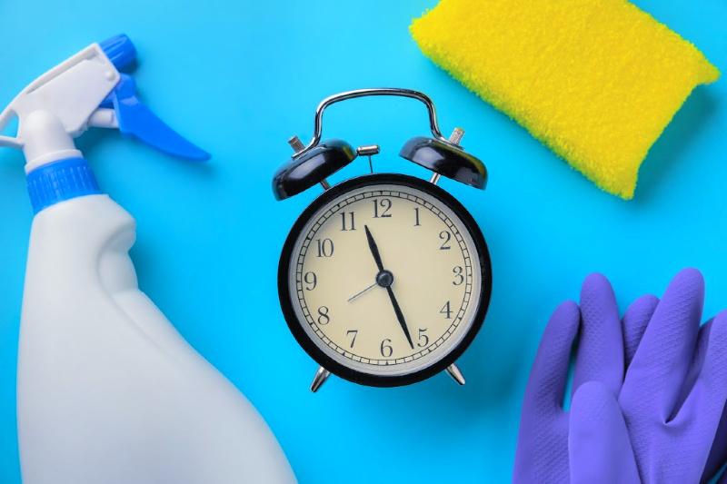 Fotografía cenital de una botella rociadora, un guante de goma y una esponja que rodea un reloj despertador de cuerda antiguo para limpiar rápidamente su casa