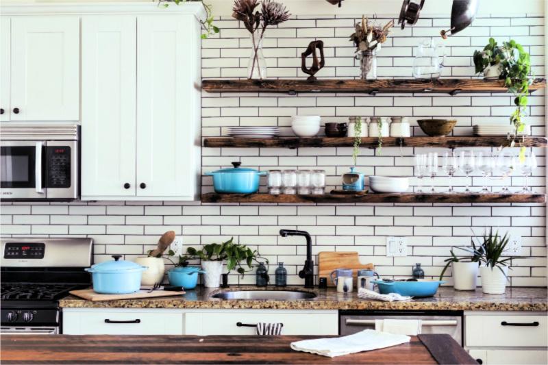 Cocina blanca moderna con estantes de madera abiertos y pared de azulejos de metro