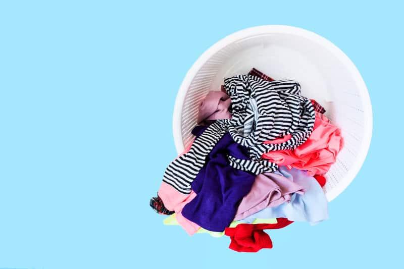 Cesta de lavandería de plástico redonda llena de ropa desordenada