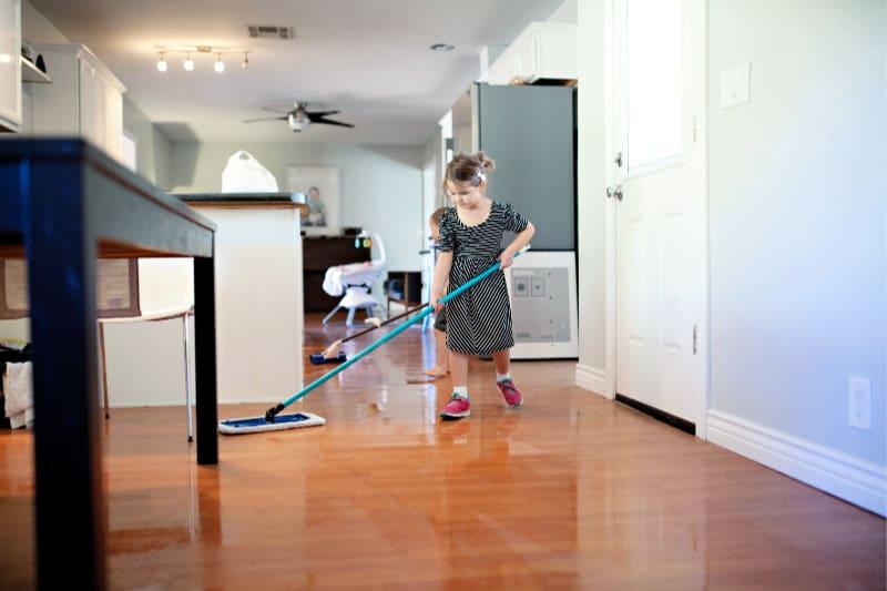 Los niños pequeños ayudando a limpiar la casa mediante el uso de trapeadores en el piso de madera