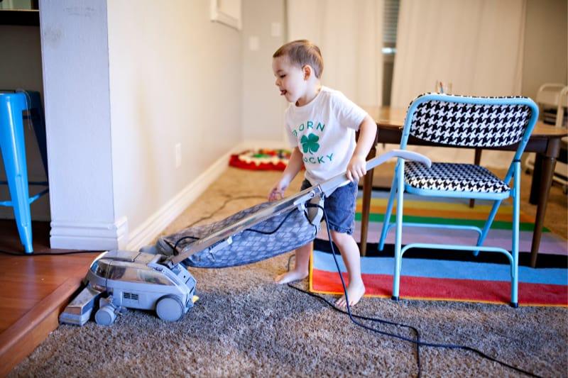 Niño ayudando a limpiar la casa aspirando el piso