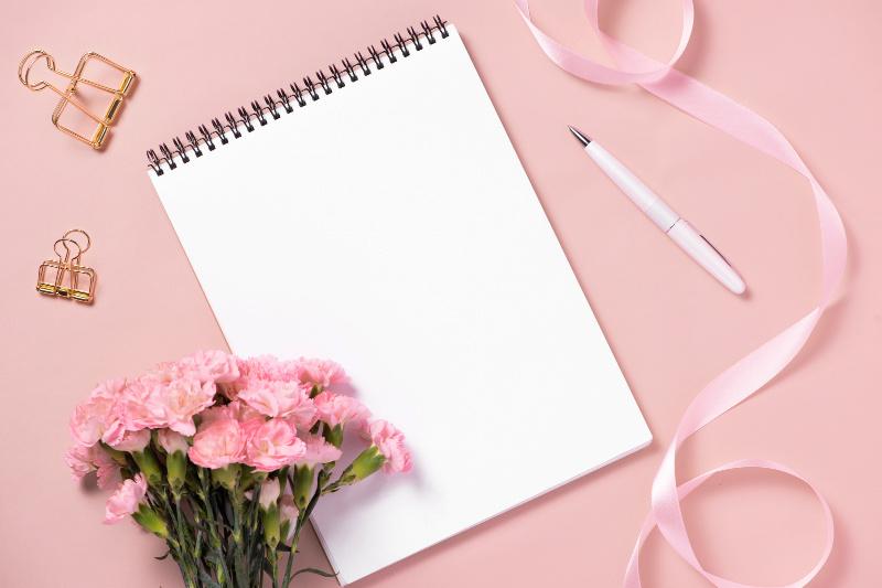 Suministros de oficina y cuaderno en blanco sobre un fondo rosa