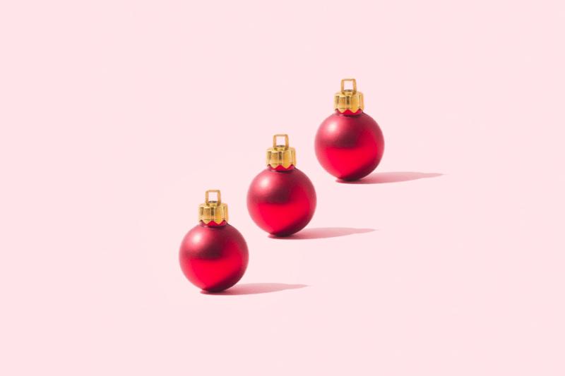 Cómo evitar el estrés navideño: adornos navideños sobre un fondo liso