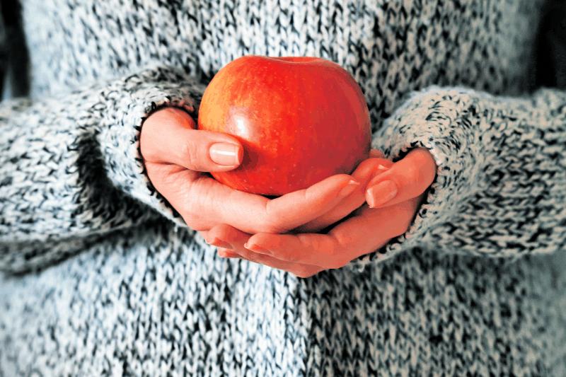 Mujer sosteniendo la manzana que simboliza el ciclo virtuoso para volver a la pista