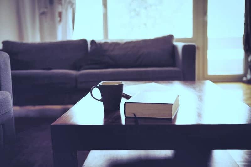 Mesa de centro de madera pulida con libro y taza de café