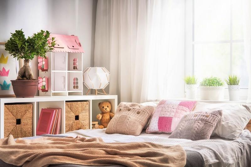 Dormitorio infantil limpio y organizado con detalles en rosa y blanco en la cama y la casa de muñecas