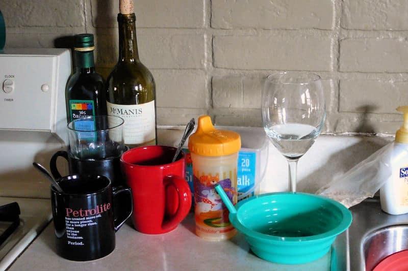 Platos sucios y una botella de vino en la cocina