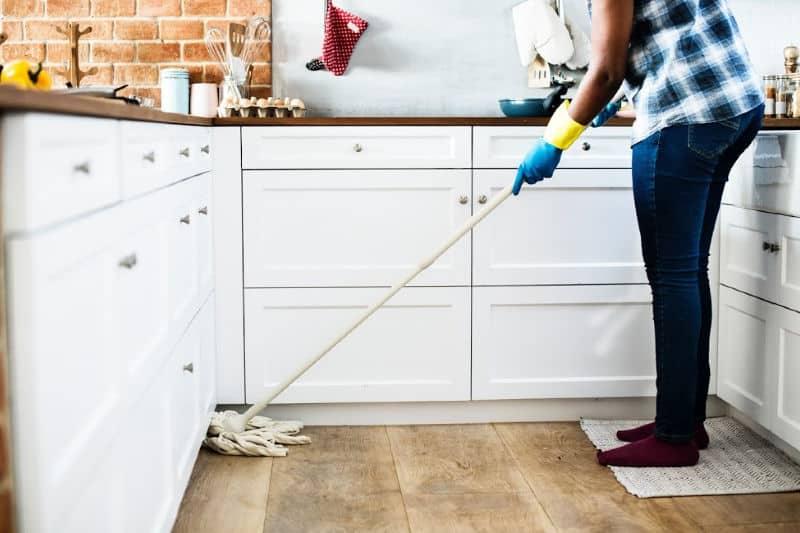 Persona trapeando el piso de la cocina
