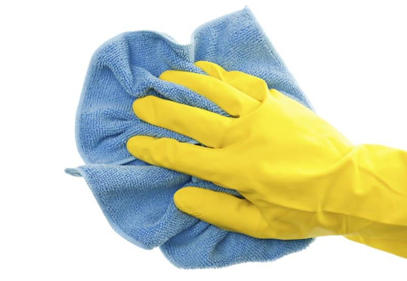 Cómo limpiar los paños de microfibra de la manera correcta: mano con guantes de limpieza de goma y con un paño de microfibra