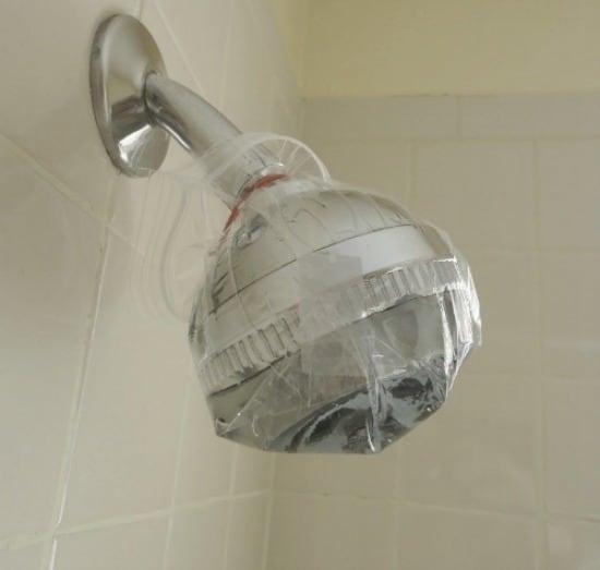 Cómo limpiar un cabezal de ducha: llene una bolsa de plástico con agua y vinagre y colóquela en el cabezal de la ducha.