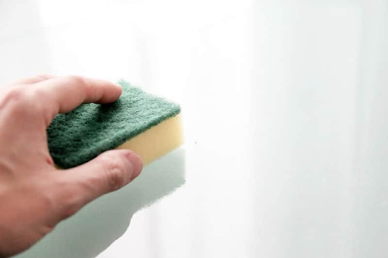 Conviértase en una persona más limpia limpiando los desorden de la cocina todas las noches: esponja de mano y mostrador de limpieza