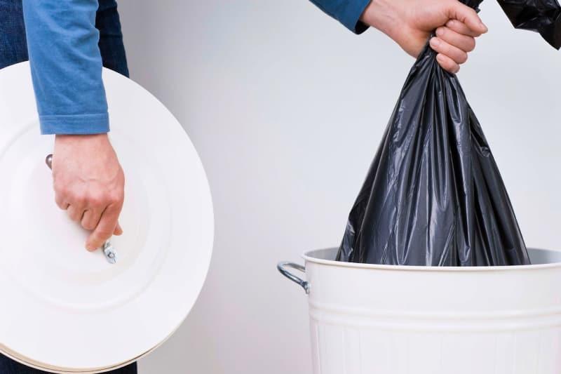 Primer plano de una persona quitando la bolsa de basura llena del bote de basura mientras sostiene la tapa