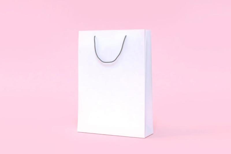 Bolsa de compras de papel blanco liso sobre un fondo de color rosa