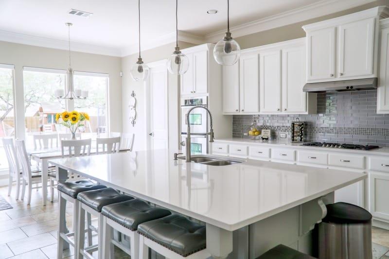 Lista de verificación de limpieza de primavera de la cocina: cocina moderna y limpia con alacenas blancas y encimera de granito