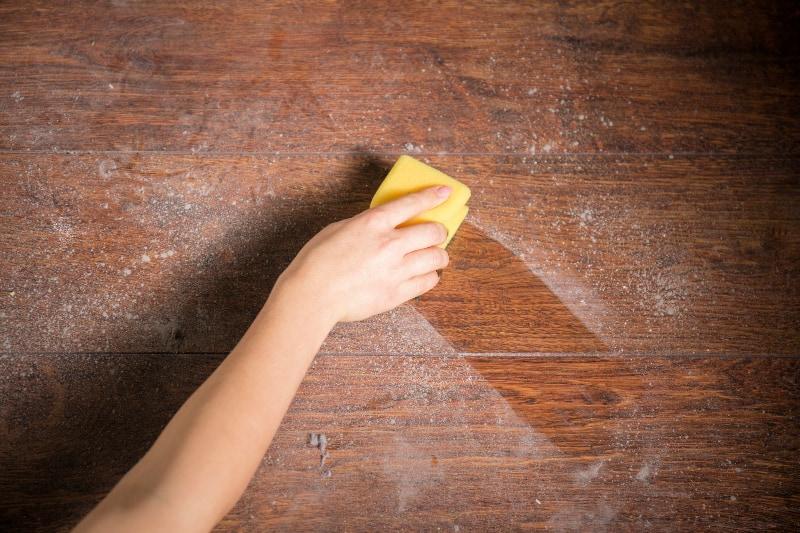 Mano sujetando una esponja para limpiar un camino limpio a través del polvo en la mesa de madera