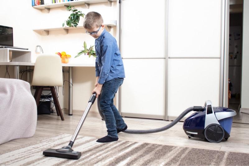Niño en edad escolar que pasa la aspiradora como parte de las tareas domésticas asignadas