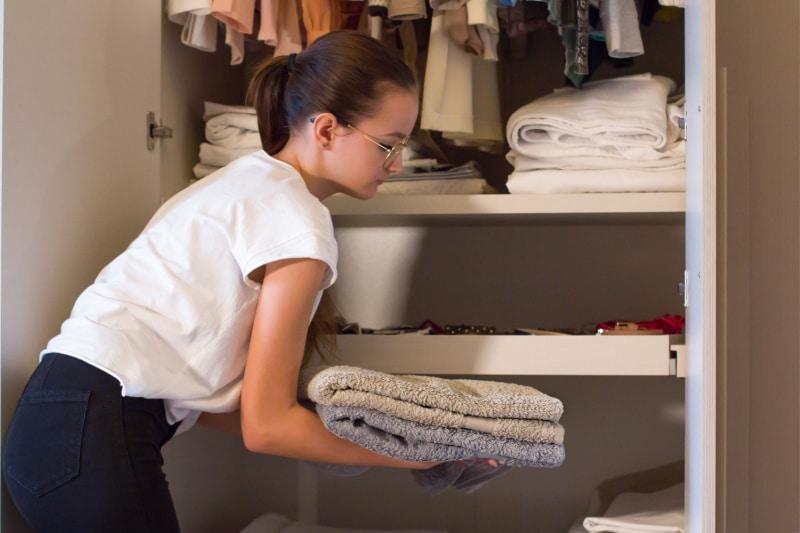 Adolescente ayudando con las tareas del hogar guardando el montón de toallas dobladas en el armario de la ropa blanca