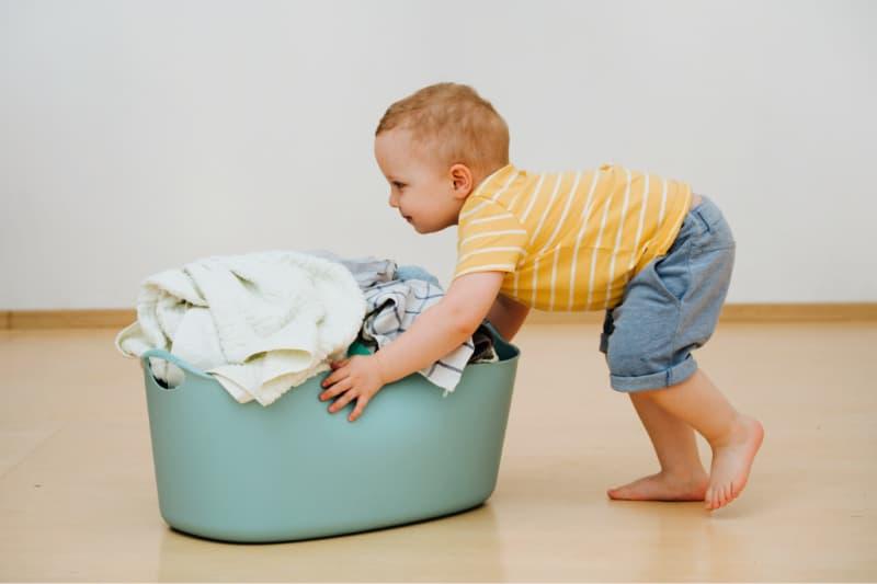 Niño empujando la canasta de lavandería como parte de las tareas del hogar