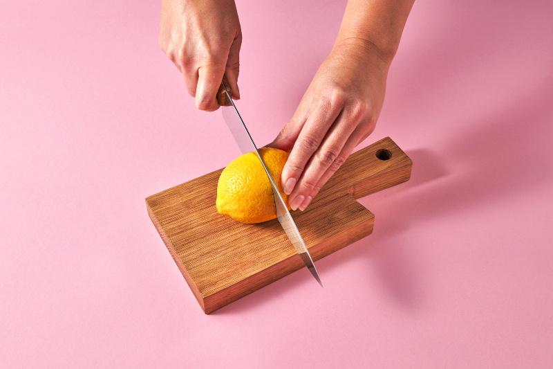 Usos de los limones: fotografía cenital de dos manos sosteniendo un limón y un cuchillo sobre una tabla de cortar de madera