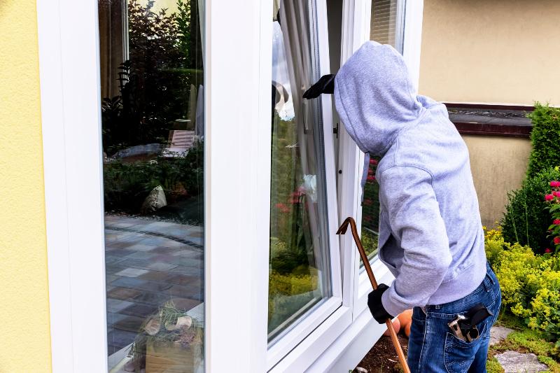 Hombre con guantes y con una palanca se asoma a la ventana de una casa.