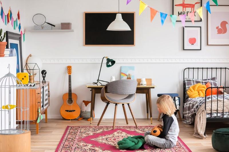 Niño sentado en el piso del dormitorio limpio lleno de muebles eclécticos
