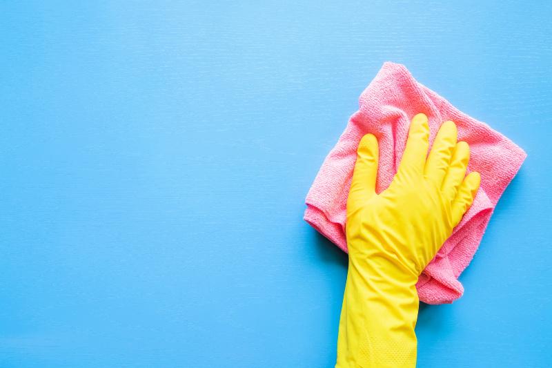 Mano en guante de goma amarillo con un paño rosa para hacer la rutina de limpieza diaria