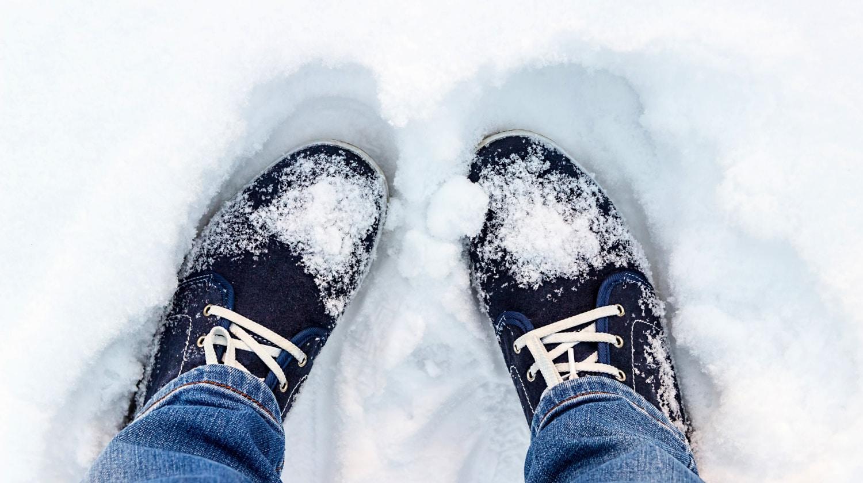 Vista aérea de pies en zapatillas azules de pie en la nieve.