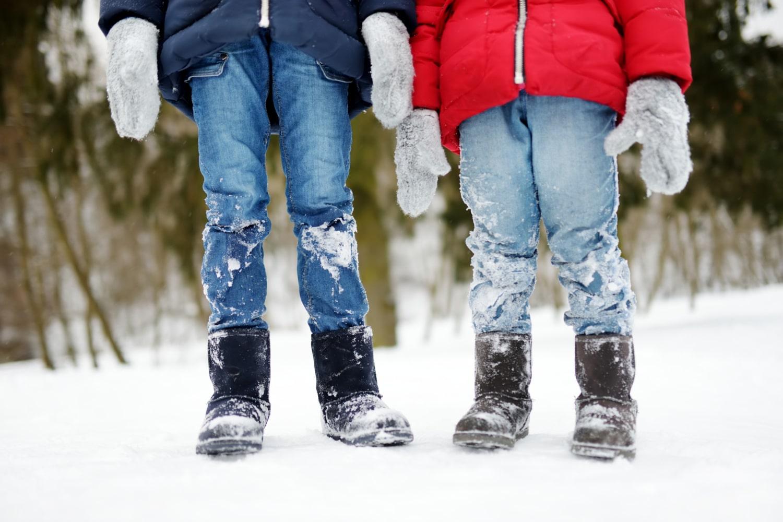 Foto de cintura para abajo de dos niños con botas de nieve Uggs y ropa de invierno